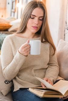 Retrato, de, um, bonito, mulher jovem, xícara café, girar, a, livro, páginas