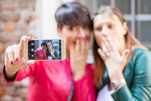 Retrato, de, um, bonito, mulheres jovens, fazendo, selfie, cidade, com, um, smartphone