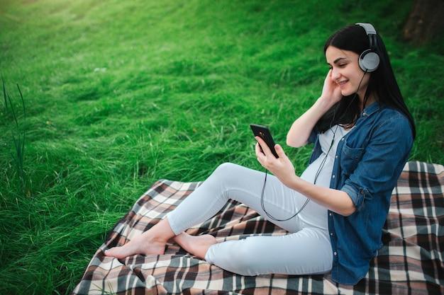 Retrato de um cabelo preto feliz e de uma mulher gravida orgulhosa em um parque. a mãe expectante está ouvindo música no parque com um nascituro