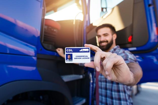 Retrato de um caminhoneiro barbudo de meia idade parado perto de seu caminhão e mostrando sua carteira de motorista comercial.