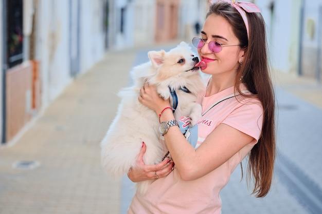 Retrato de um cão pomeranian macio branco que lambe o rosto da moça.