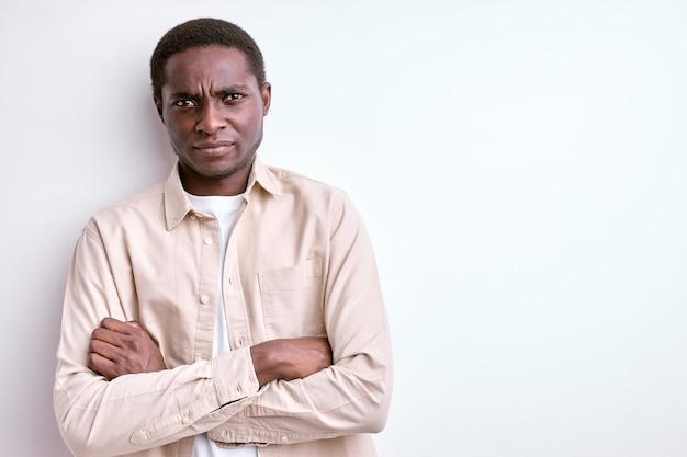 Retrato de um cara africano confiante em pé com os braços cruzados e cara de raiva séria