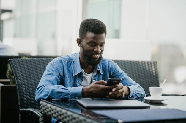 Retrato de um cara africano falando no telefone com o laptop na frente dele na mesa