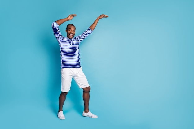 Retrato de um cara afro-americano entusiasmado dançando loucamente, levantando as mãos