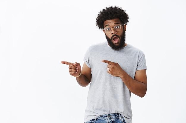 Retrato de um cara afro-americano maduro e animado, com cabelo encaracolado e barba aberta, empolgado, apontando para a esquerda com espanto e surpresa