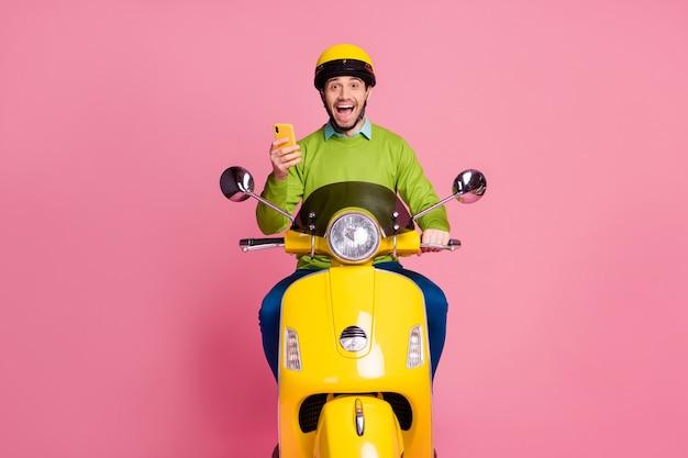 Retrato de um cara alegre positivo andando de moto usando o celular