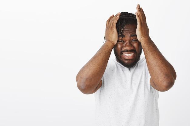 Retrato de um cara ansioso com tranças posando contra a parede branca
