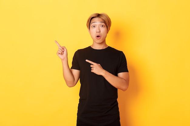 Retrato de um cara asiático bonito impressionado e animado em uma camiseta preta, reagindo ao seu logotipo, apontando o dedo no canto superior esquerdo
