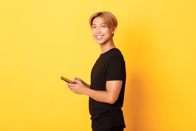 Retrato de um cara asiático elegante e bonito em roupa preta, usando o celular e virando a cabeça com um sorriso satisfeito, parede amarela