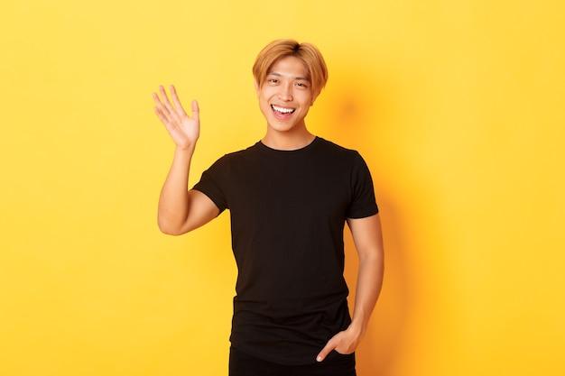 Retrato de um cara asiático simpático e bonito em roupa preta, acenando com a mão para dizer olá e sorrindo, cumprimentando alguém, em pé na parede amarela