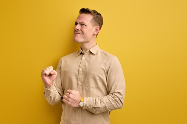 Retrato de um cara atraente, alegre, alegre, contente, mostrando um gesto vencedor isolado no amarelo