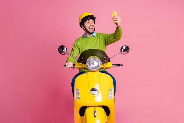 Retrato de um cara atraente e alegre andando de moto, tirando uma selfie no telefone