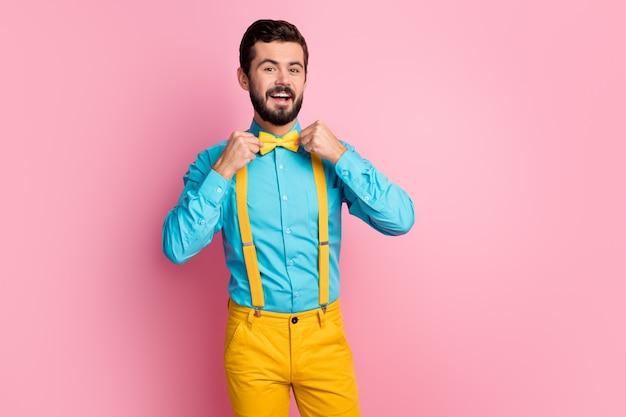 Retrato de um cara barbudo alegre e alegre consertando uma gravata borboleta