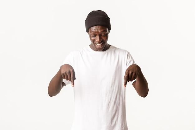 Retrato de um cara bonito afro-americano feliz e divertido no gorro, olhando e apontando o dedo para algo interessante