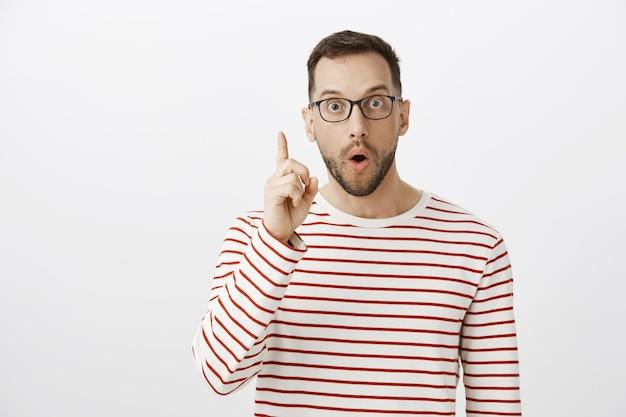 Retrato de um cara bonito animado de óculos escuros, tendo uma ideia e levantando o dedo indicador em um gesto de eureca
