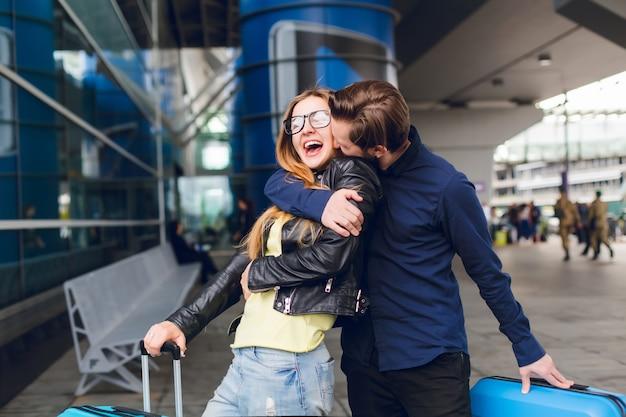 Retrato de um cara bonito com barba na camisa preta, beijando a garota com cabelo comprido lá fora no aeroporto. ela usa óculos, suéter amarelo e jaqueta com jeans. ela parece feliz.