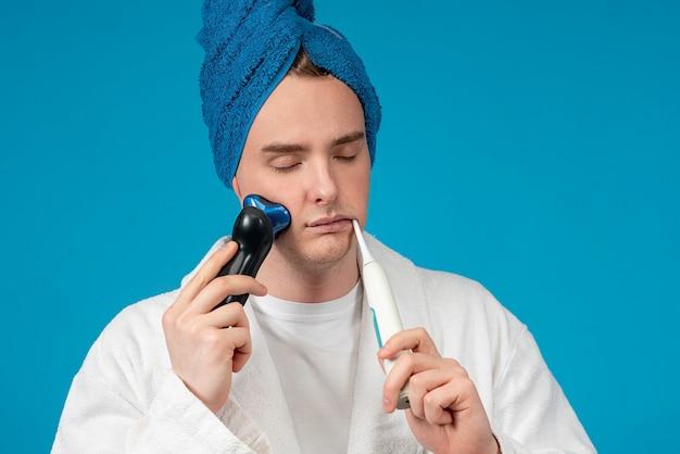 Retrato de um cara bonito com sono, jovem com os olhos fechados com uma toalha na cabeça, fazendo a rotina matinal, escovando os dentes com escova de dentes elétrica e barbeando o rosto, barba com máquina de barbear, navalha. higiene
