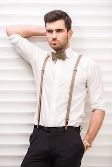 Retrato de um cara bonito com suspensórios e gravata borboleta.