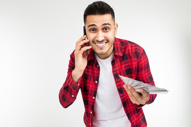 Retrato de um cara bonito com um monte de dinheiro falando ao telefone em um estúdio branco com espaço de cópia