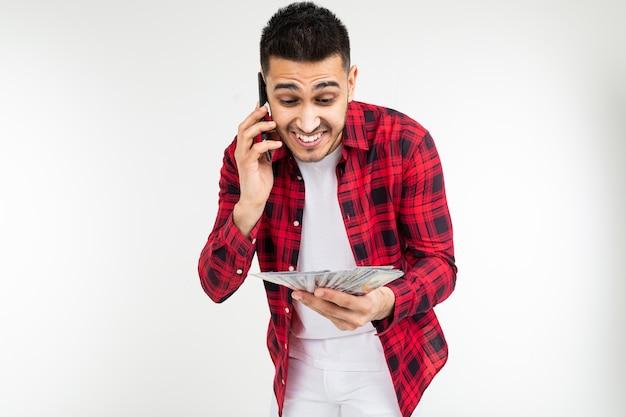 Retrato de um cara bonito com um monte de dinheiro falando ao telefone em um fundo branco studio com espaço de cópia