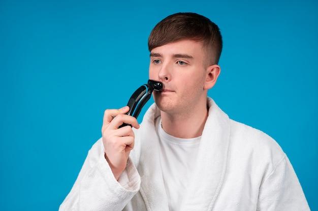 Retrato de um cara bonito e atraente, jovem com roupão de banho branco raspando a barba, bigode