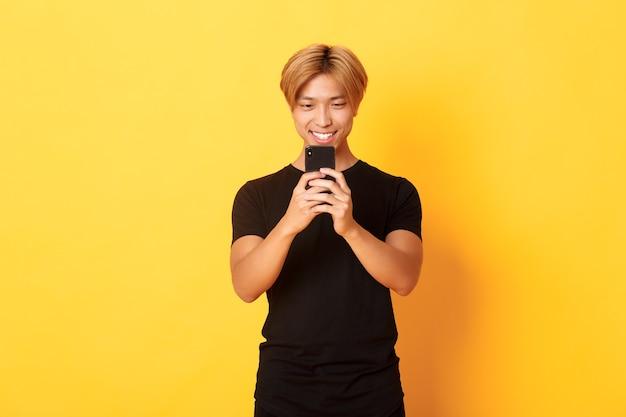 Retrato de um cara bonito e elegante asiático com cabelo loiro, usando telefone celular e sorrindo, enviando mensagens no aplicativo para smartphone, parede amarela