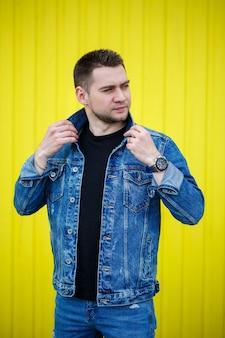 Retrato de um cara bonito e elegante, um homem vestido com uma camiseta preta em branco de pé sobre um fundo de parede amarela. estilo urbano de roupas, imagem na moda moderna. moda masculina