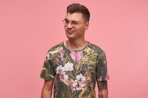 Retrato de um cara bonito em uma camiseta com estampa floral, olhando para a câmera e dando uma piscadela, sendo glamour e brincalhão, posando sobre fundo rosa