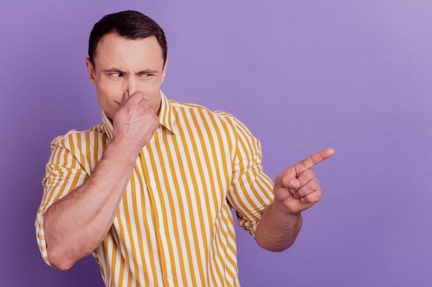 Retrato de um cara chateado e enojado com o dedo indicador direto e o nariz coberto de espaço vazio em fundo roxo