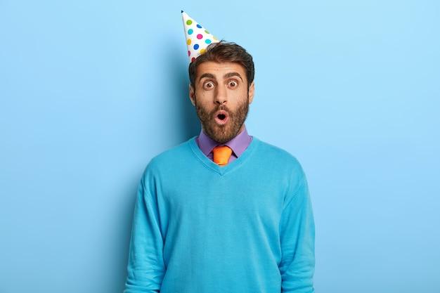 Retrato de um cara com a barba por fazer chocado usando chapéu de festa