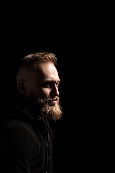 Retrato de um cara com barba no escuro