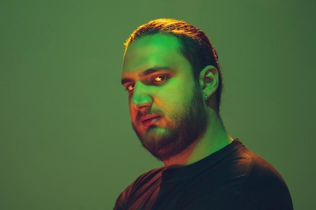 Retrato de um cara com luz de néon colorida na parede verde. modelo masculino com humor calmo e sério. expressão facial, estilo de vida e aparência de millenials. futuro, tecnologias.
