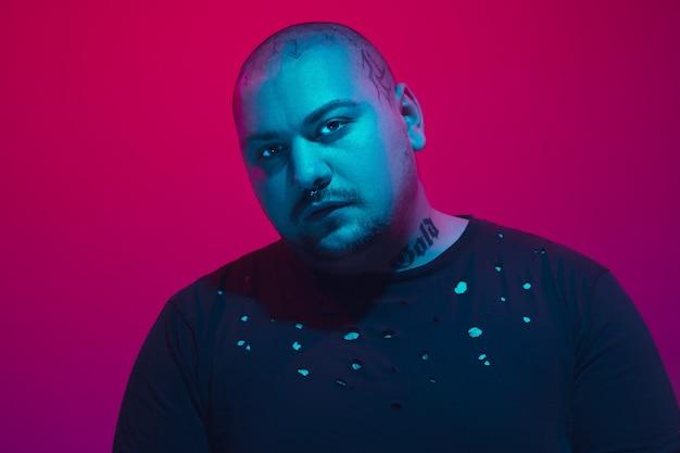 Retrato de um cara com luz de néon colorida na parede vermelha. modelo masculino com humor calmo e sério. expressão facial, estilo de vida e aparência de millenials. futuro, tecnologias.