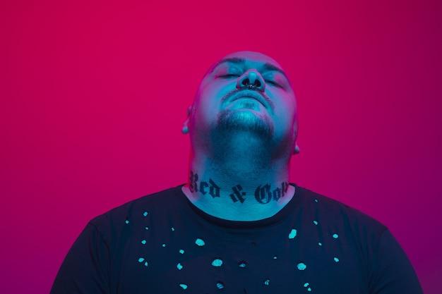 Retrato de um cara com luz de néon colorida no conceito cyberpunk de fundo vermelho