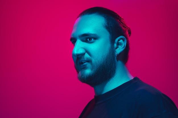 Retrato de um cara com luz de néon colorida no fundo rosa do estúdio. modelo masculino com humor calmo e sério.