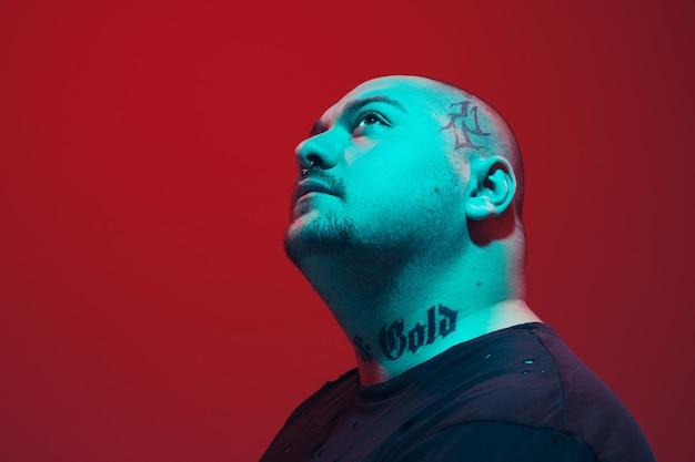 Retrato de um cara com luz de néon colorida sobre fundo vermelho do estúdio. modelo masculino com humor calmo e sério.