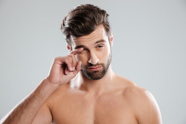 Retrato de um cara com sono nu, coçar o olho