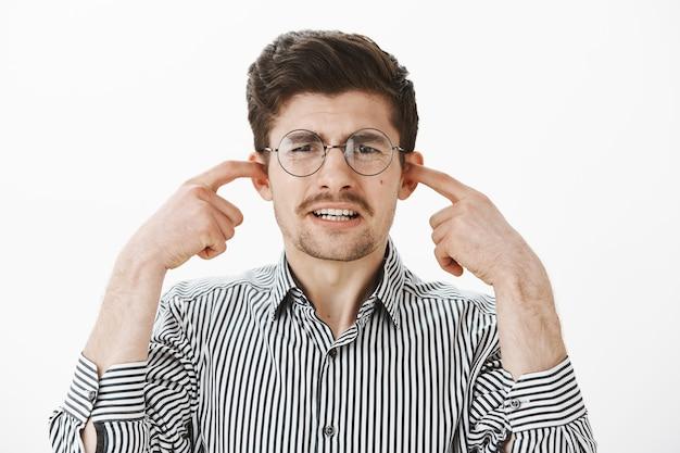 Retrato de um cara comum choramingando chateado de óculos redondos e camisa listrada, cobrindo as orelhas com o dedo indicador, fazendo uma expressão de desagrado, sentindo antipatia ao ouvir um arranhão horrível no quadro-negro