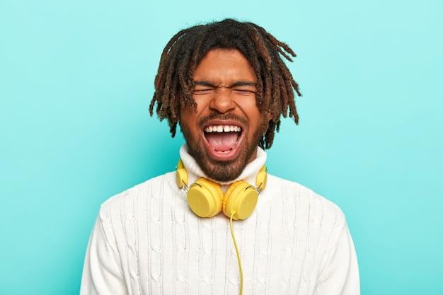 Retrato de um cara de pele escura grita emocionalmente, mantém a boca bem aberta, os olhos fechados, usa um suéter branco quente, fones de ouvido no pescoço