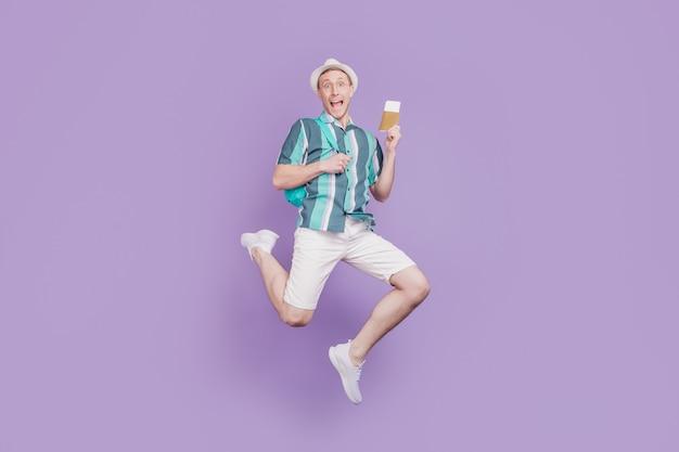 Retrato de um cara de turista positivo e funky espantado, salto, corrida, passaporte de ingressos, sobre fundo violeta
