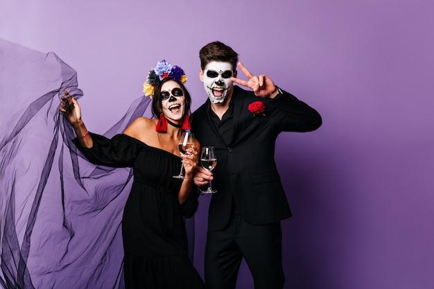 Retrato de um cara engraçado e uma garota com rostos pintados, se divertindo com taças de vinho na festa de halloween.
