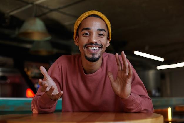 Retrato de um cara feliz, adorável, de pele escura, de olhos castanhos e barba, olhando alegremente e levantando as mãos emocionalmente, demonstrando seus dentes brancos perfeitos sobre o interior do café