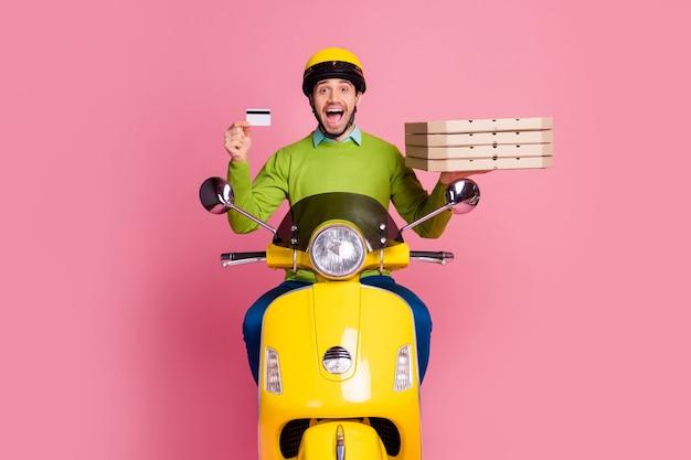 Retrato de um cara feliz andando de ciclomotor segurando nas mãos o cartão do banco