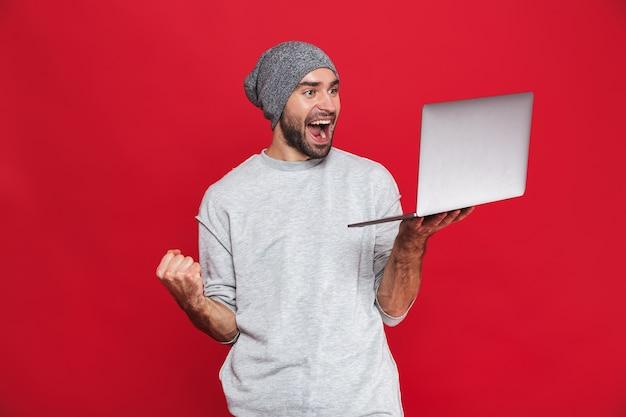 Retrato de um cara feliz dos 30 anos em roupa casual se regozijando enquanto segura um laptop prateado isolado