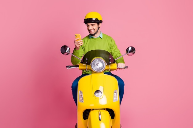 Retrato de um cara focado andando de moto usando o celular