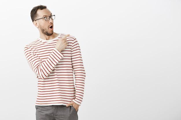 Retrato de um cara fofo surpreso e satisfeito com um pulôver listrado e óculos