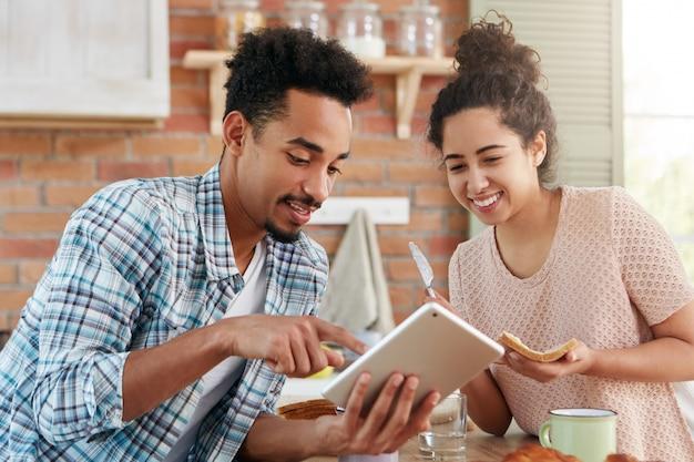 Retrato de um cara hippie de raça mista mostra algo em um computador tablet para sua esposa, que está ocupada fazendo sanduíches