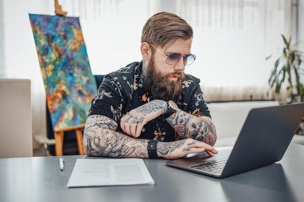 Retrato de um cara hippie em uma camisa preta com tatuagens e óculos de sol se senta à mesa com uma cara séria, fazendo seu trabalho no laptop em casa.