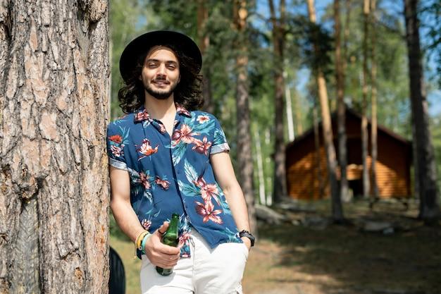 Retrato de um cara hippie positivo com uma camisa de flores e chapéu apoiado na árvore e segurando uma garrafa de cerveja na floresta