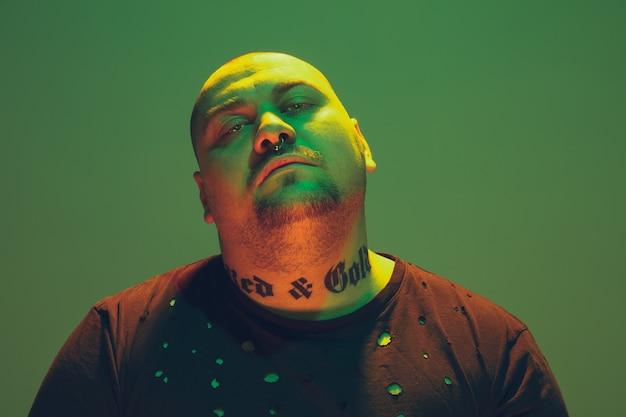 Retrato de um cara hipster com luz de néon colorida na parede verde. modelo masculino com humor calmo e sério.